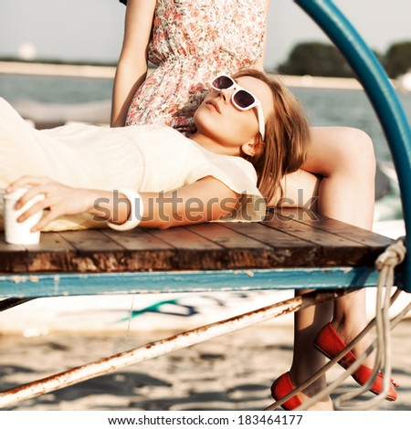 beautiful tanned girl in yellow summer dress with a to-go cup sleeps on her girlfriend's knee on wooden bridge under water - stock photo