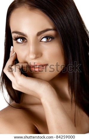 beautiful tanned Italian woman touching her face applying cream and smiling over white background - stock photo