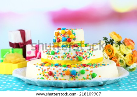 Beautiful tasty birthday cake and gifts on light background - stock photo