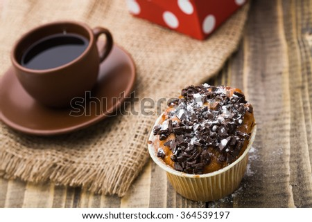 Beautiful tasty muffin with chocolate on top near brown cup of strong fragrant coffee standing on sackcloth napkin appetizing refreshment break time closeup on wooden background, horizontal picture - stock photo