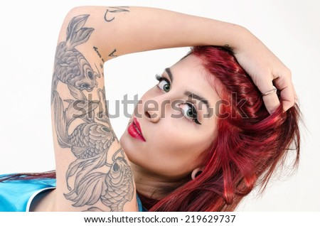 Beautiful tattooed Girl with red hair. tattoo - stock photo