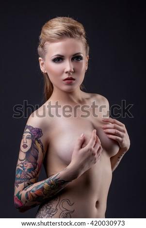 Beautiful tattooed model posing nude at camera - stock photo