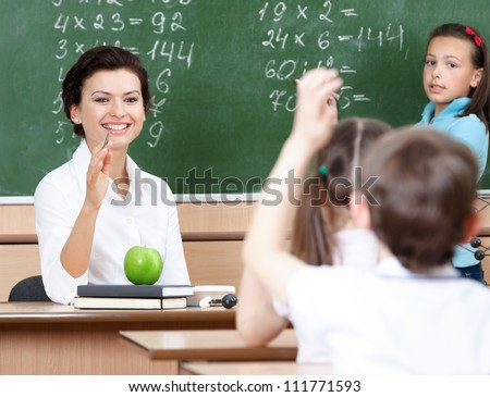 Beautiful teacher questions pupils at algebra - stock photo