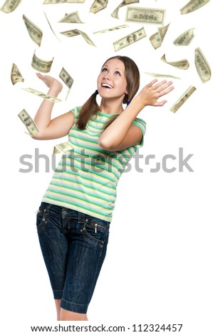 Beautiful teen girl catching falling dollars banknotes on white background - stock photo
