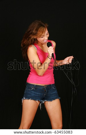 beautiful teen girl singing with microphone on black background - stock photo