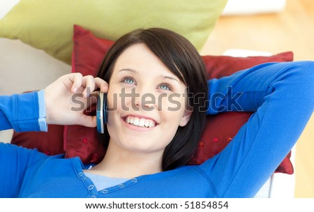 Beautiful teen girl talking on phone lying on a sofa in the living-room - stock photo