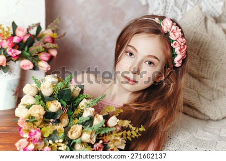Beautiful teen girl with a bouquet of spring flowers in home interior. The concept of a happy childhood. - stock photo
