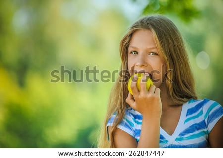 Beautiful teenage girl biting an apple, against green of summer park. - stock photo