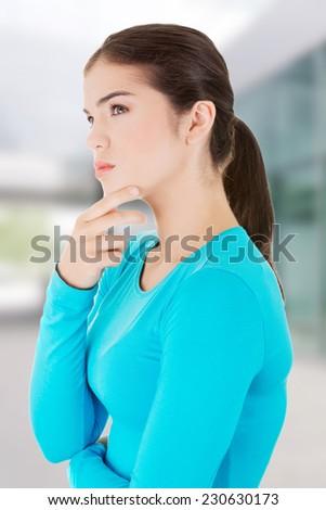 Beautiful teenage girl is thinking - stock photo