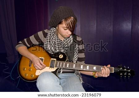 Beautiful teenage girl playing an electric guitar. - stock photo