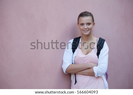 Beautiful teenage girl poses with a book and her arms crossed - stock photo