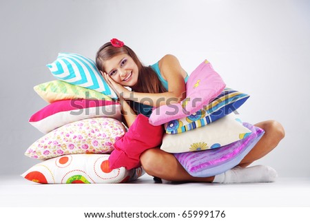 Beautiful teenage girl resting on pillows studio shot - stock photo
