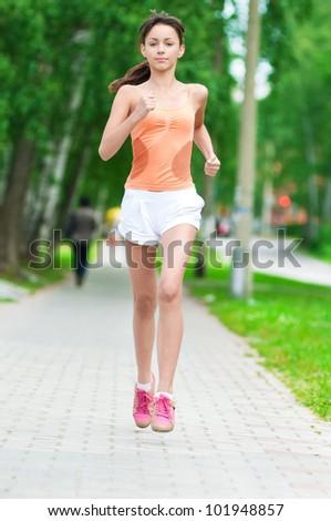 Beautiful teenage girl running in green park on sunny summer day - stock photo