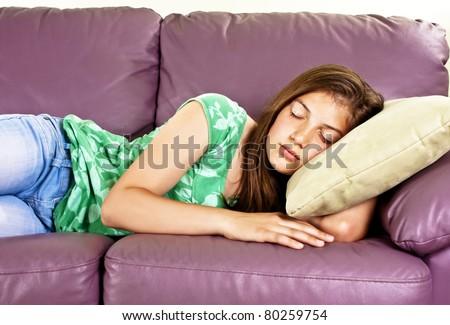 Beautiful teenage girl sleeping on sofa - stock photo