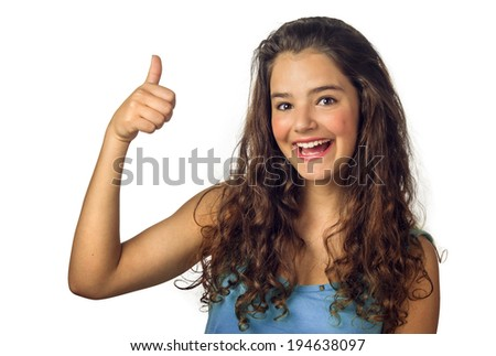 Beautiful teenage girl smiling and doing the thumbs-up sign - stock photo