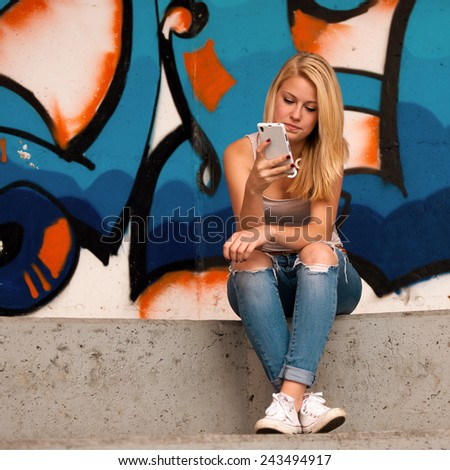 Beautiful teenage girl speaks on a cell phone - stock photo