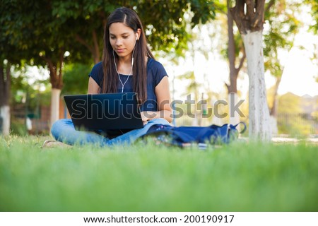 Beautiful teenage girl using a laptop and earbuds outdoors - stock photo
