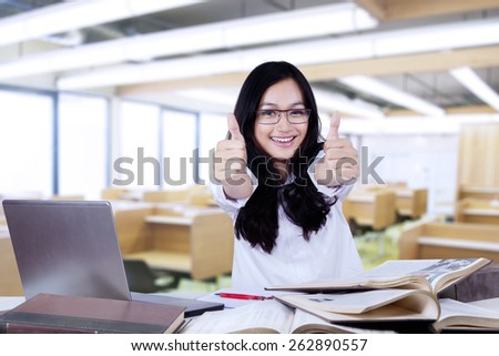 Beautiful teenage girl with black hair smiling at the camera while showing thumbs up in the classroom - stock photo