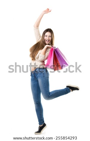 Beautiful teenage girl with broad happy smile jumping with joy, holding heap of shopping bags. Sale, discount, fashion, profitable offer concepts - stock photo