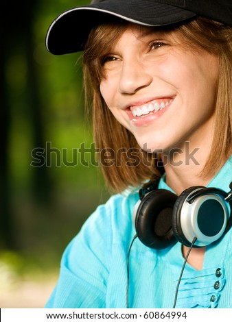 Beautiful teenage girl with headphones in the green park - stock photo