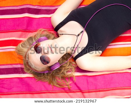 Beautiful Teenage Girl with headphones lying on her back on a colorful rug listening to music - stock photo