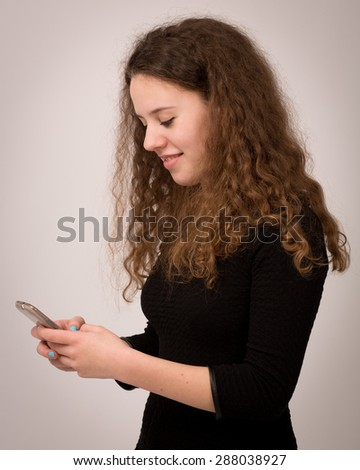 Beautiful teenage girl with long curly ginger hair sending text messages on her phone. - stock photo
