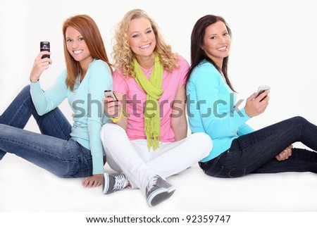 Beautiful teenage girls are holding cell phones - stock photo