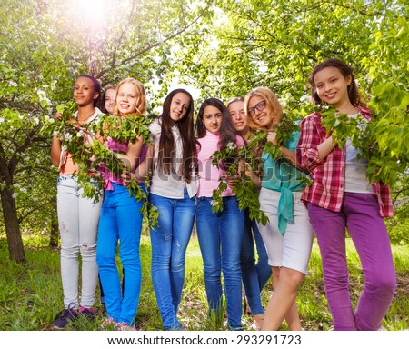 Beautiful teenage girls hold benches with leaves - stock photo