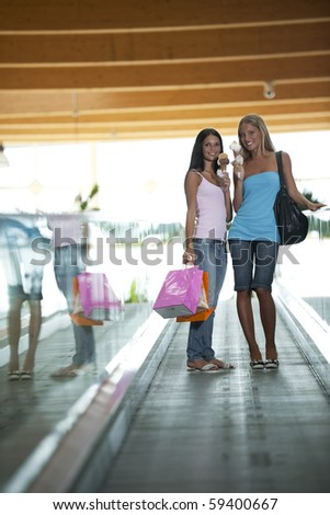 Beautiful teenage girls on escalator at shopping center, eating ice-cream - stock photo