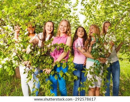 Beautiful teenage girls stand, hold green benches - stock photo