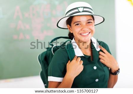 beautiful teenage schoolgirl carrying backpack in classroom - stock photo