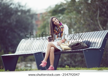 beautiful teenage student girl sitting in park with smart phone and coffee cup - stock photo
