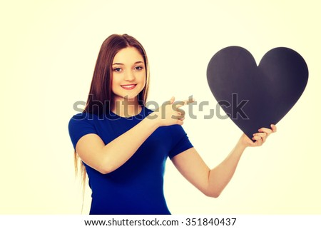 Beautiful teenage woman pointing on paper heart. - stock photo