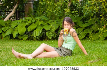 Beautiful teenager girl drinking tea in the park, sitting on grass - stock photo
