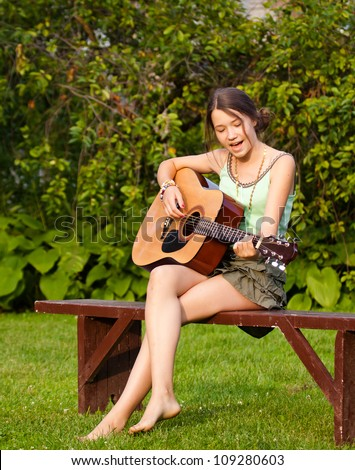 Beautiful teenager girl singing and playing the guitar in the park - stock photo