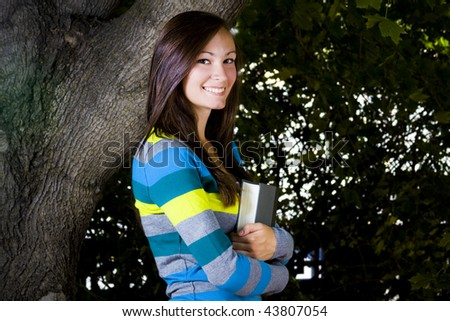 Beautiful Teenager holding a book with Leaves in the Background - stock photo