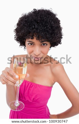 Beautiful teenager holding a glass of champagne while looking at the camera - stock photo