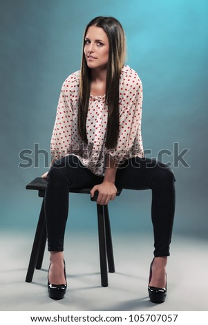 beautiful teenager sitting on a stool in blue light wearing black jeans - stock photo