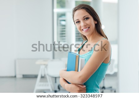Beautiful teenager student girl smiling at camera and holding books, education and learning concept - stock photo
