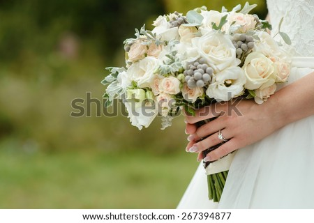 beautiful tender wedding bouquet of cream roses and eustoma flowers in hands of the bride - stock photo