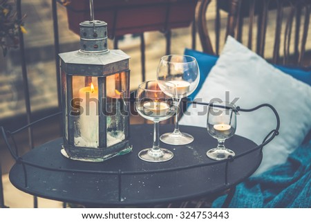 Beautiful terrace or balcony with cozy rattan armchair and candles on small iron table on small iron table. Toned picture - stock photo