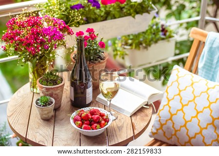 Beautiful terrace or balcony with small table, chair and flowers - stock photo