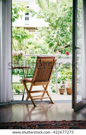 Beautiful terrace or balcony with small table, chair and flowers. Garden view - stock photo