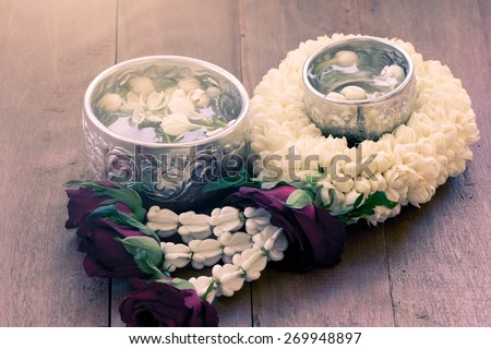 beautiful Thai garland flowers (jasmine and roses) and water in bowl (Use for Songkran festival in Thailand) in soft color - stock photo