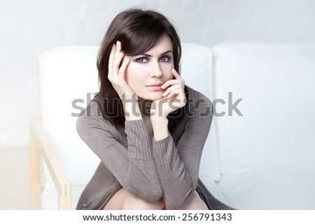 beautiful thoughtful girl sits on a sofa - stock photo