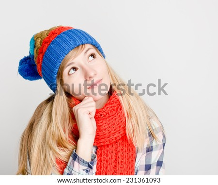 Beautiful thoughtful woman looking up in winter hat - stock photo