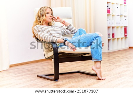 Beautiful thoughtful young woman sitting relaxed in white armchair. Interior. - stock photo