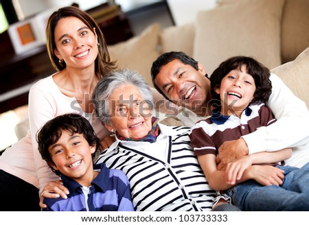 Beautiful three-generation family smiling at home - stock photo