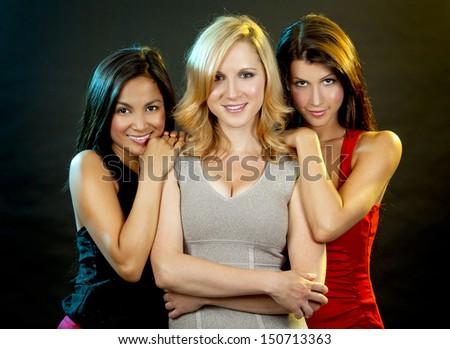 beautiful three women having fun during party on dark background - stock photo