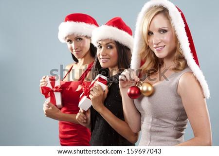 beautiful three women wearing christmas hats on blue background - stock photo